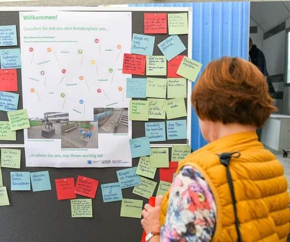 Frau schaut sich ein Board mit Notizen bei einer Moderationsveranstaltung von ISR Haan an