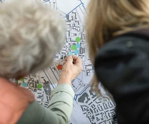 Frau setzt einen farbigen Punkt auf eine Karte bei ISR Haan