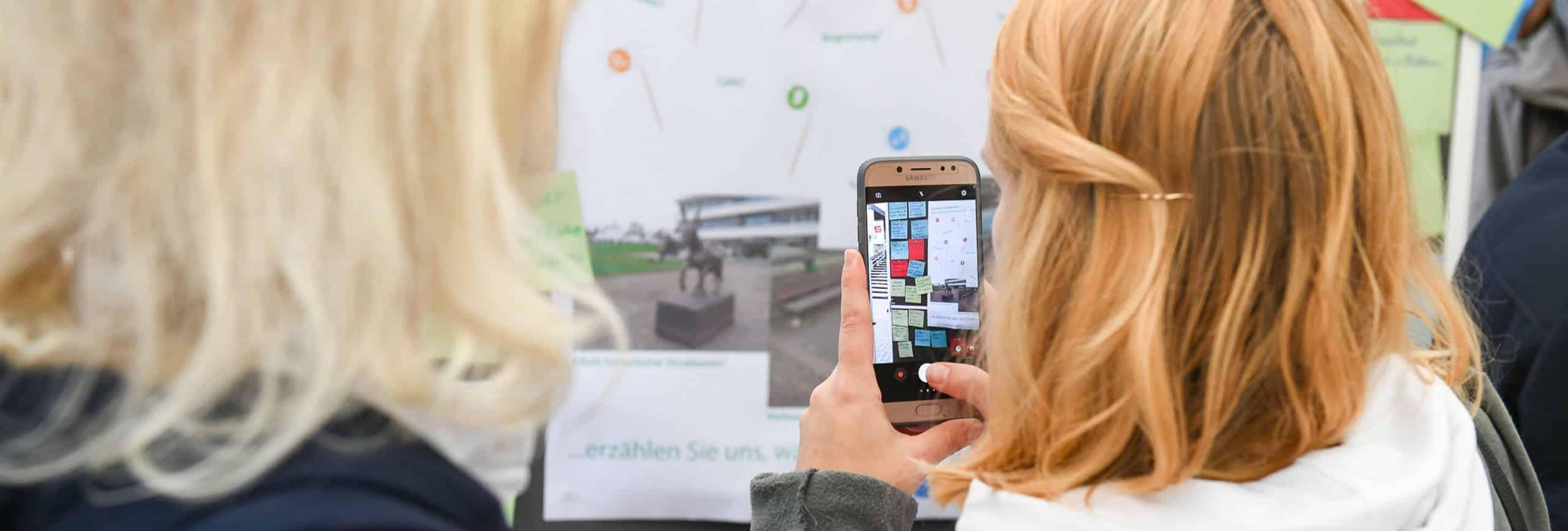 Blonde Frau macht ein Foto bei einer Moderationsveranstaltung