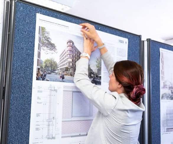 Mitarbeiterin von ISR Haan beim aufhängen eines Plakates zum Wettbewerbsmanagement
